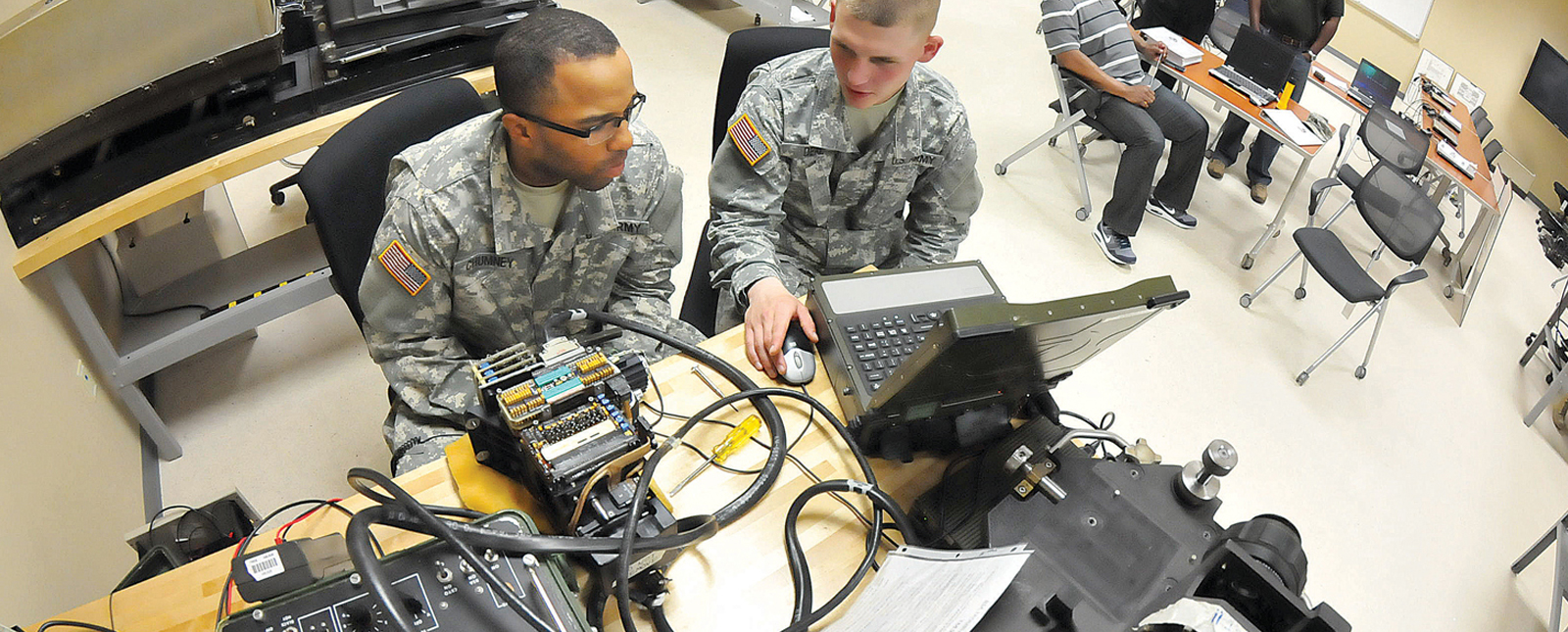 Two military personnel in a classroom / electronic lab setup.